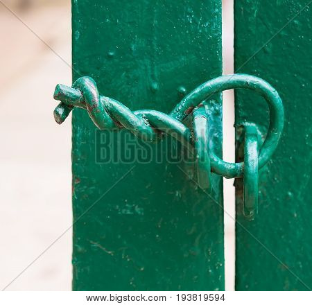 Green fence. The gate is closed. There is no lock. The door is closed with a twisted wire