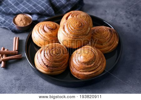 Black round plate with yummy cinnamon rolls on kitchen table