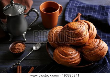 Round plate with yummy cinnamon rolls on kitchen table
