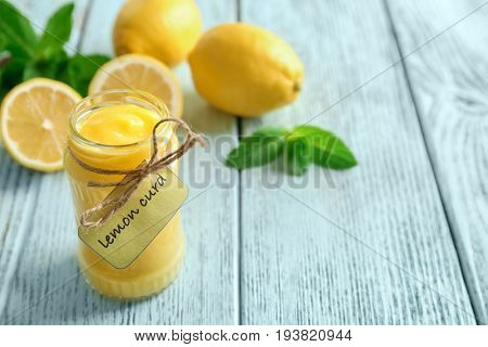 Glass jar with yummy lemon curd on wooden table