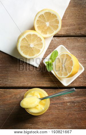 Composition with yummy lemon curd in glass jar on wooden table