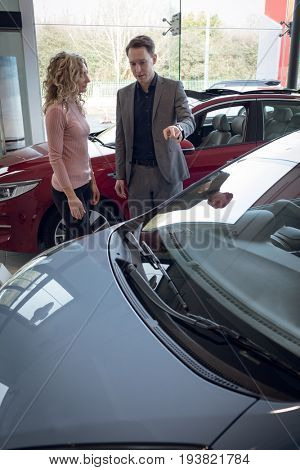 Female customer looking at salesman showing car while standing in showroom
