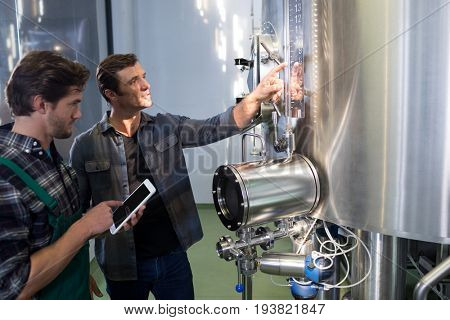 Worker explaining to coworker using tablet computer at brewery
