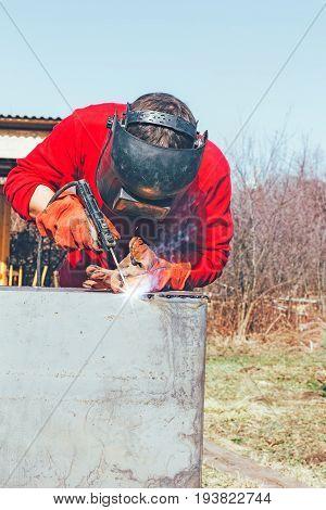 Welder puts a seam on metal electro arc welding photo toning