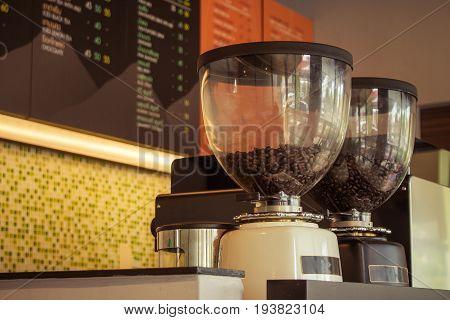 Coffee beans in coffee grinder preparing to grind coffee at coffee shop. (Vintage filter effect)