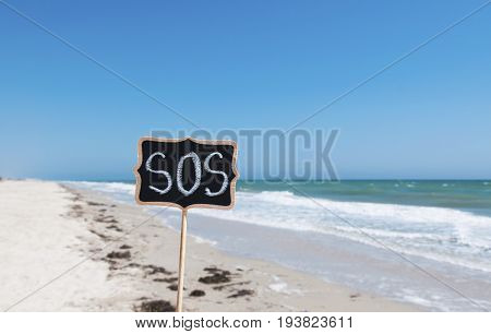 wooden signpost with the inscription SOS close up