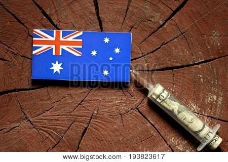 Australian Flag On A Stump With Syringe Injecting Money In Flag