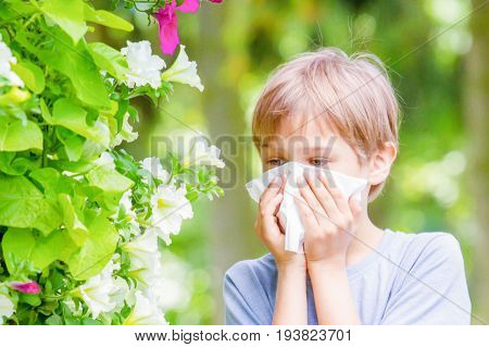 Allergy. Child is blowing his nose near tree in bloom.