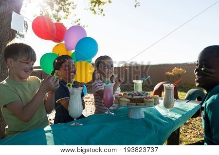 Happy children talking while having food and drinks against sky at table in park