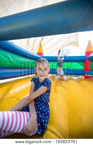 Portrait of happy girl sitting on bouncy castle while brother doing handstand in background