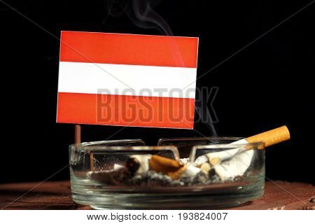Austrian Flag With Burning Cigarette In Ashtray Isolated On Black Background