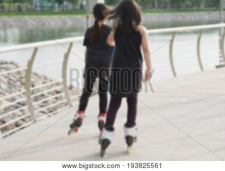 Blurred young people playing roller skates outdoor in park. Teenage girls on roller skates at outdoor.
