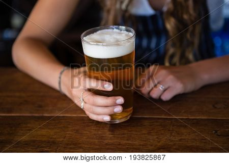 Midsection of barmaid with beer glass at wooden counter in bar