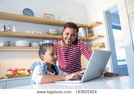 Mother and daughter using laptop in kitchen worktop at home