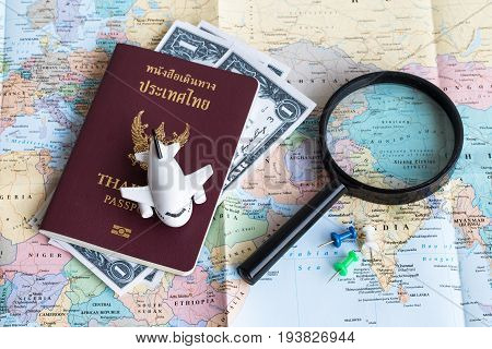 A Passport Of Thai Citizen With Money, Pin, Magnifying Glass And Mini Airplane  Model On A Map, Worl
