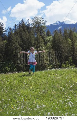 Excited girl with arms outstretched running in park