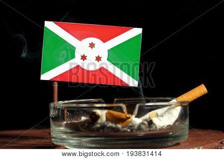 Burundi Flag With Burning Cigarette In Ashtray Isolated On Black Background