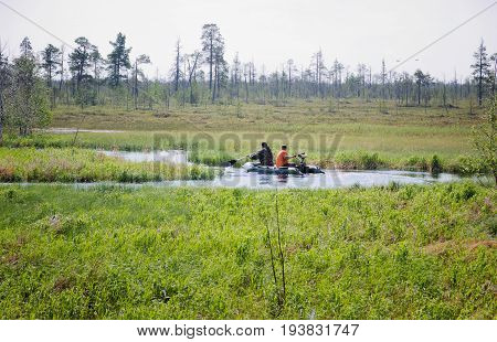 Two men in an inflatable boat floating on a meandering swampy river in the Siberian tundra