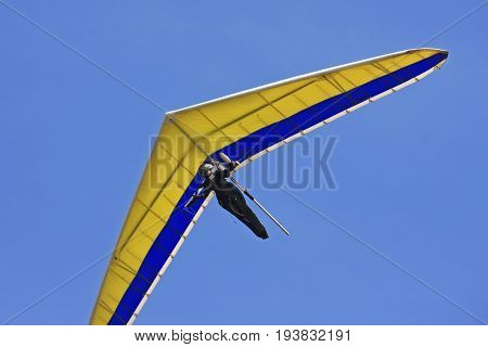 Hang glider flying his wing in a blue sky