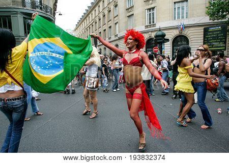 Paris France - Jun 27 2015: A Brazilian transsexual dances with the Brazilian flag during the annual Gay Pride Parade in Paris France.