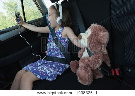 Cute girl taking selfie with teddy bear from mobile phone in car