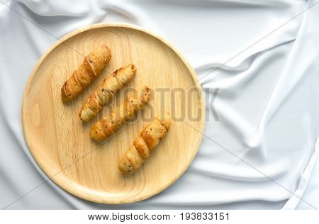Pastry on wooden plate on white cloth background take photo top view have copy space easy to use for graphic work