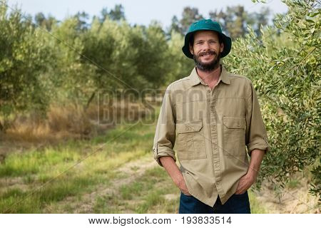 Portrait of smiling farmer standing with hands in pocket in olive farm