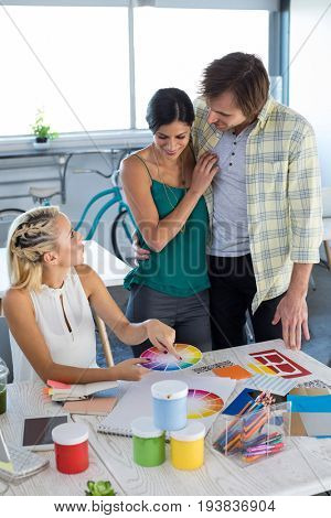 Executives looking at color shade swatch in office