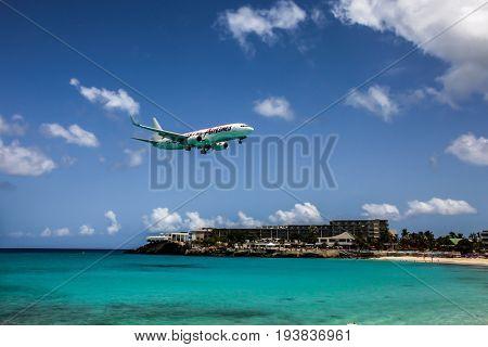 ST. MAARTEN-AUGUST 1:  Aeroplane Caribbean Airlines is landing on Princess Juliana International Airport, over Maho Bay Beach seen in St.Martin/St.Maarten on August 1, 2015
