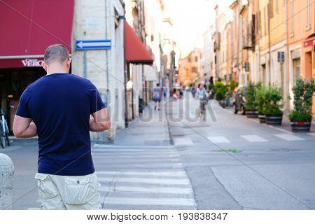 Ferrara, Italy - June, 30, 2017: pedestrian crosses on a street in a center of Ferrara, Italy