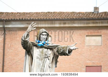 Ferrara, Italy - June, 30, 2017: monument of Girolamo Savonarola in Ferrara, Italy with the blue scarf for fun tied to it