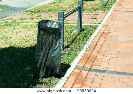 Black plastic garbage bag on the street as a garbage can.