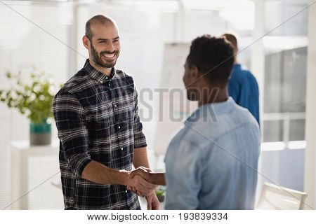 Happy business partners shaking hands in the office