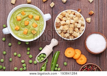 Green Peas Soup In Plate With Rusks On Wooden Table