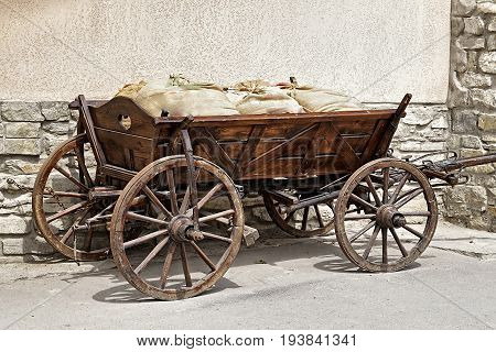 Medieval transport - a cart with bags near wall (without horses). Ancient cargo transportation.