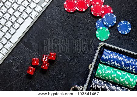 Poker set in a metallic case and keyboard on a grey table top view.