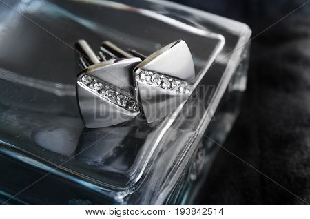Silver cufflinks with precious stones lie on a bottle of perfume black background horizontal photo composition in the center