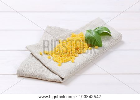 pile of small pasta shells on beige place mat