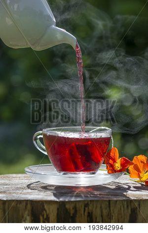 a cup of fruity tea on a garden table