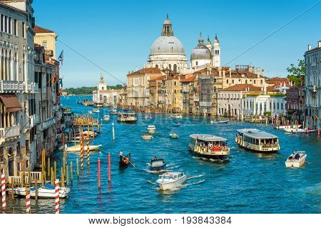 Venice, Italy - May 18, 2017: Transport traffic on the Grand Canal. Santa Maria della Salute church in the distance. Grand Canal is one of the major water-traffic corridors in Venice.