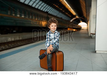 Boy with wavy hair dressing in check suit sitting on orange suitcase at railroad platform.