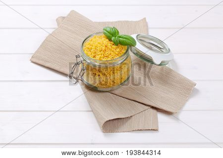 jar of small pasta shells on beige place mat