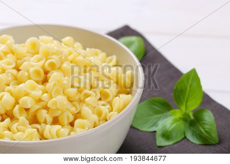 bowl of small pasta shells on dark grey place mat - close up