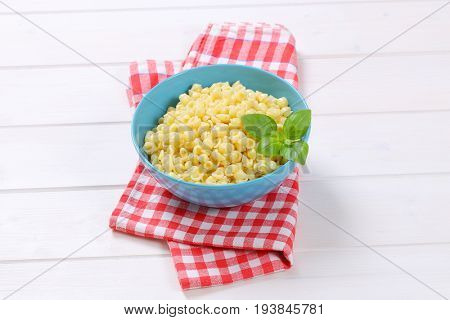 bowl of small pasta shells on checkered dishtowel