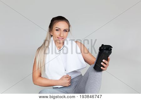 Smiling blonde woman with towel around neck in sporty clothing sitting on floor holding shaker.