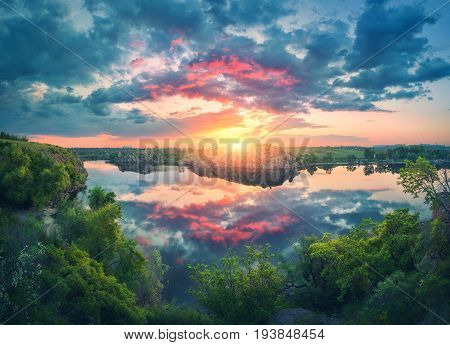 Amazing scene with river, green trees, rocks and amazing blue sky with colorful clouds reflected in water at sunset. Fantastic summer landscape with lake, overcast sky and yellow sun in the evening