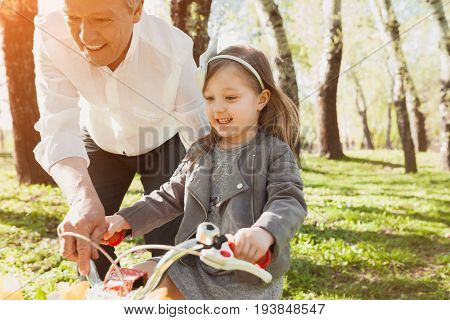 Grandfather with his young granddaughter teaching how to ride a bike in park on sunny day.