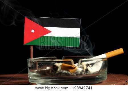 Jordanian Flag With Burning Cigarette In Ashtray Isolated On Black Background
