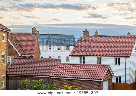 Modern housing estate UK. Variety of homes and garage buildings against cloudscape sky.