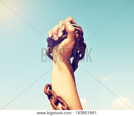 The female hand is lifted up and bound by an iron chain against the sky and the sun